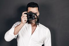 Young handsome photographer with beard and mustache studio portr. Young handsome photographer with beard and mustache holding a dslr camera, studio portrait Royalty Free Stock Images