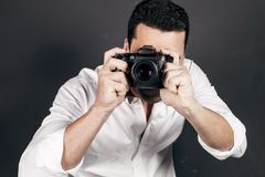Young handsome photographer with beard and mustache studio portr. Young handsome photographer with beard and mustache holding a dslr camera, studio portrait Stock Photos