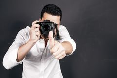 Young handsome photographer with beard and mustache studio portr. Young handsome photographer with beard and mustache holding a dslr camera, studio portrait Royalty Free Stock Photography