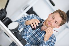 Young handsome photographer cleaning gear royalty free stock images