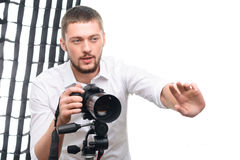 Young handsome photographer while giving. Working moments. Young attractive professional photographer gestures while giving directions to the model stock photo