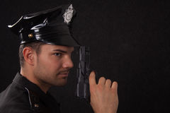 Young handsome policeman with gun Royalty Free Stock Image