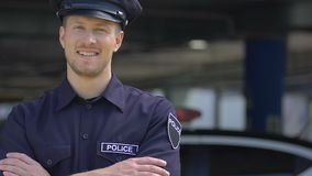 Young handsome policeman smiling, happy to serve for city security, recruitment. Stock footage stock video footage