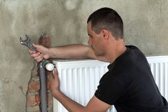 Young handsome professional plumber worker installing heating radiator on brick wall using a wrench in an empty room of a newly bu stock photo