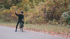 Young handsome professional triathlete in black cycling clothes, black helmet and glasses on road bicycle in autumn forest taking. Selfie on phone. Triathlon stock video footage