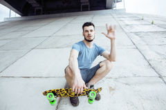 Young handsome real hipsrter guy bearded staying under the bridge extreeme with leopard skateboard, lifestyle people Royalty Free Stock Images