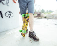 Young handsome real hipsrter guy bearded staying under the bridge extreeme with leopard skateboard, lifestyle people Stock Images