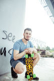 Young handsome real hipsrter guy bearded staying under the bridge extreme with leopard skateboard, lifestyle people Royalty Free Stock Photo
