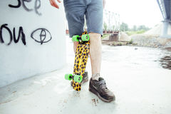 Young handsome real hipsrter guy staying under the bridge extreeme with leopard skateboard, lifestyle people concept Royalty Free Stock Photo