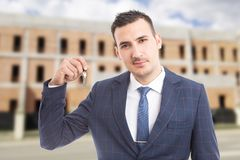 Young handsome realtor holding house keys. Young handsome realtor or real estate agent holding house keys as new home sale on outdoor building background Stock Photos