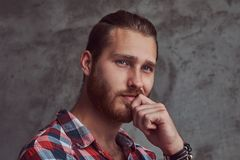 Young handsome redhead model man in a flannel shirt on a gray background. royalty free stock photography