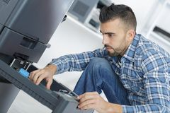 Young handsome repairer fixing photocopier. Man Stock Photography