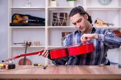 Young handsome repairman repairing guitar royalty free stock images