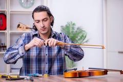 Young handsome repairman repairing violin royalty free stock image