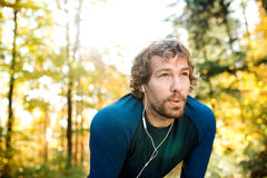 Free Young Handsome Runner With Earphones Outside In Autumn Nature Royalty Free Stock Images - 77930629
