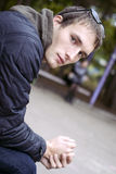Young handsome sad man seating on bench in park Royalty Free Stock Photos