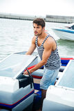 Young handsome sailor man driving his motor boat Stock Photo