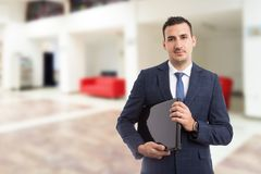 Young handsome salesman holding laptop. Young handsome salesman or broker holding laptop as technology communication or work concept, on indoor lobby background royalty free stock photography