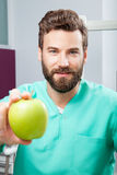 Young handsome serious male doctor with beard holding green apple Stock Images