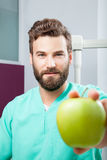 Young handsome serious male doctor with beard holding green apple Royalty Free Stock Images