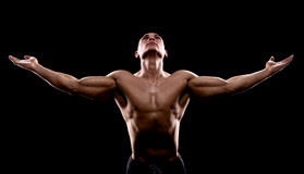 Young handsome sexy bodybuilder looking up on a dark background Stock Photography