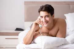Young handsome shirtless guy showing nude torso sexy on bed at h Royalty Free Stock Photography