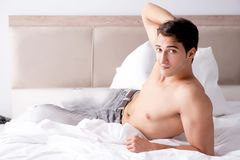 Young handsome shirtless guy showing nude torso sexy on bed at h Stock Photos