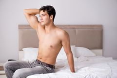 Young handsome shirtless guy showing nude torso sexy on bed at h Royalty Free Stock Photos