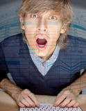 Young handsome shocked good looking man. Portrait of young handsome shocked good looking man working using keyboard and looking at camera through the screen of stock images