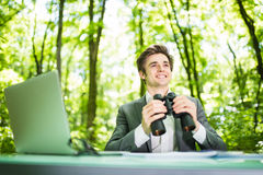 Young handsome smile business man at work table office with laptop in green forest with binocular looking for competitors. Busines Royalty Free Stock Photos
