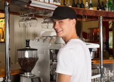 Young handsome smiling barista in white shirt and baseball hat s. Tanding bihend the counter next to the commercial grade coffeemaker. Large heavy duty espresso royalty free stock photos