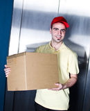 Young  handsome smiling delivery man with box. Postman is making a delivery near office elevator Royalty Free Stock Photos