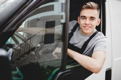 A young handsome smiling guy wearing uniform is looking out of the car window. House move, mover service royalty free stock photo