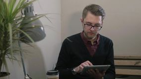 Young handsome smiling man with glasses having cup of coffee using tablet at the cafe. Young man having cup of coffee using tablet at the cafe stock video