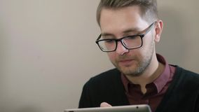 Young handsome smiling man with glasses having cup of coffee using tablet at the cafe. Young man having cup of coffee using tablet at the cafe stock footage