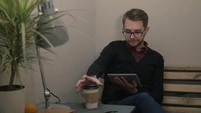 Young handsome smiling man with glasses having cup of coffee using tablet at the cafe stock video