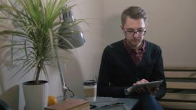 Young handsome smiling man with glasses having cup of coffee using tablet at the cafe stock footage