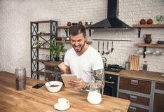 Young handsome smiling man is having his breakfast cereals with milk at the kitchen and reading morning news on the tablet been stock photos