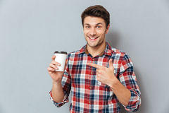 Young handsome smiling man pointing finger at takeaway coffee cup. Over gray background Stock Photography