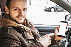 Young handsome smiling man showing smartphone or cellphone white screen as mock up for your product sitting in car. Transportation and new internet technology royalty free stock photos