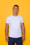 Young Handsome Smiling Man In White T-shirt. Smiling young man in white t-shirt standing and looking at camera. Three quarter length studio shot on yellow stock photography