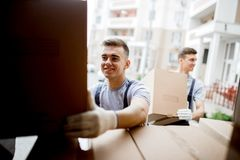 A young handsome smiling mover wearing uniform is reaching for the box while unloading the van full of boxes. House move royalty free stock photos
