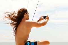 A young handsome sports guy with long hair does selfie on a smartphone on the deck of a tourist boat.  Royalty Free Stock Photography