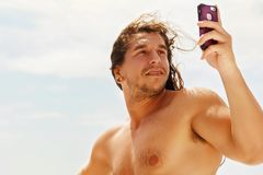 A young handsome sports guy with long hair does selfie on a smartphone on the deck of a tourist boat. A young handsome sports guy with long hair does selfie on Royalty Free Stock Photo