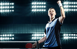 Young handsome sportsman celebrating flawless. Portrait Of Young Man Celebrating Flawless Victory in Table Tennis On Dark Background with lights stock photos