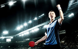 Young handsome sportsman celebrating flawless victory in table tennis. Portrait Of Young Man Celebrating Flawless Victory in Table Tennis On Dark Background with Royalty Free Stock Photo