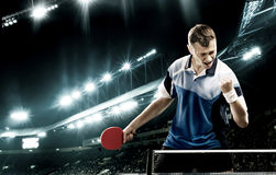 Young handsome sportsman celebrating flawless victory in table tennis. Portrait Of Young Man Celebrating Flawless Victory in Table Tennis On Dark Background with Royalty Free Stock Image