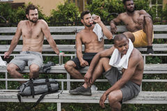 Young handsome sportsmen sitting and resting after game Royalty Free Stock Images