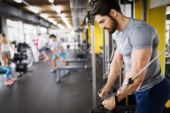 Young handsome man doing exercises in gym royalty free stock photo