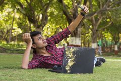 Young handsome student laying on grass, taking selfie with laptop. Young handsome student laying on grass and taking selfie with laptop Royalty Free Stock Photography